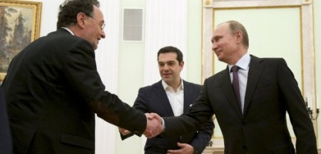 Russian President Putin shakes hands with Greek Energy Minister Lafazanis, as Prime Minister Tsipras stands nearby, during a meeting in Moscow